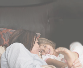 Mom and daughter laughing in bed