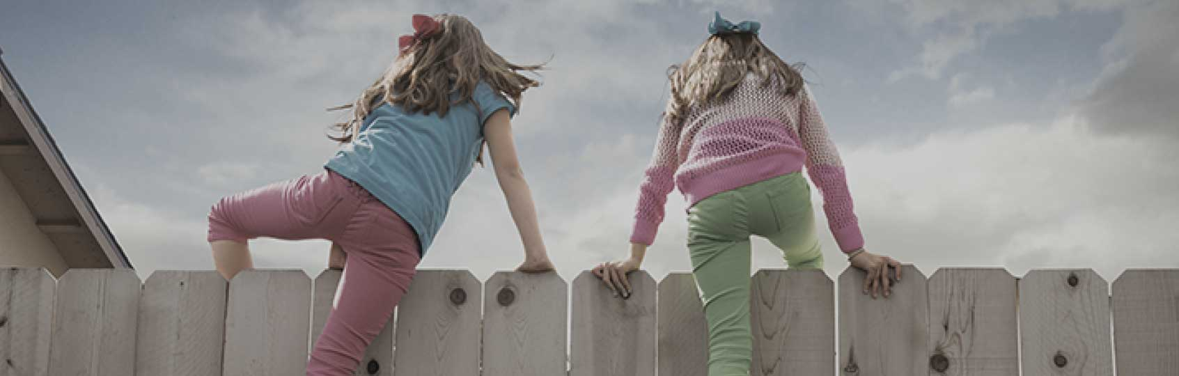 Girls climbing over a fence